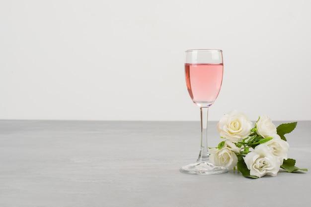 Rosas brancas e um copo de vinho rosé na mesa cinza.