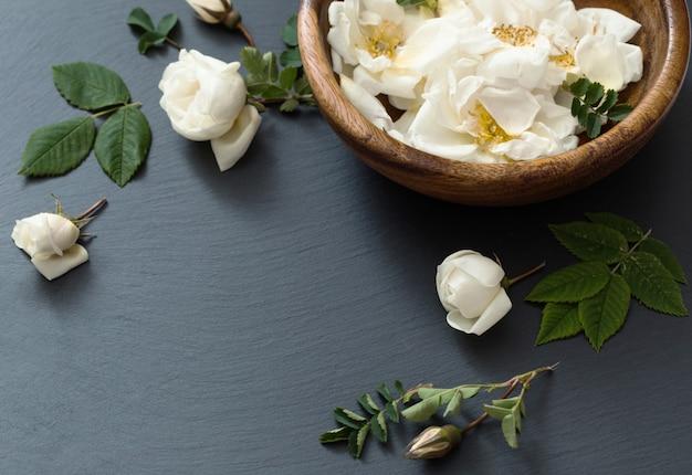 Rosas brancas em fundo preto de pedra