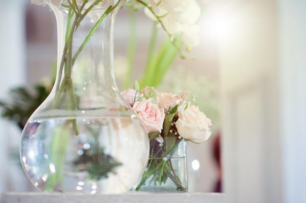 Rosas brancas em vasos de vidro transparente