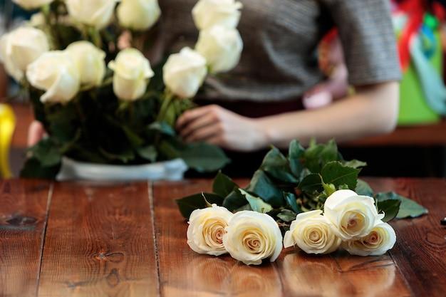 Rosas brancas mentem sobre uma mesa de madeira.