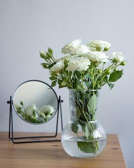 Rosas brancas no vaso de flores com mirrow no fundo cinza da mesa de mesa de madeira no estúdio. vista lateral vertical