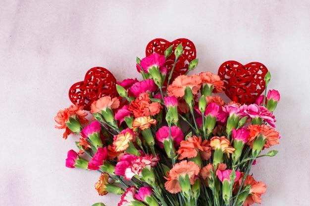 Rosas brilhantes sobre um fundo rosa e três corações vermelhos openwork