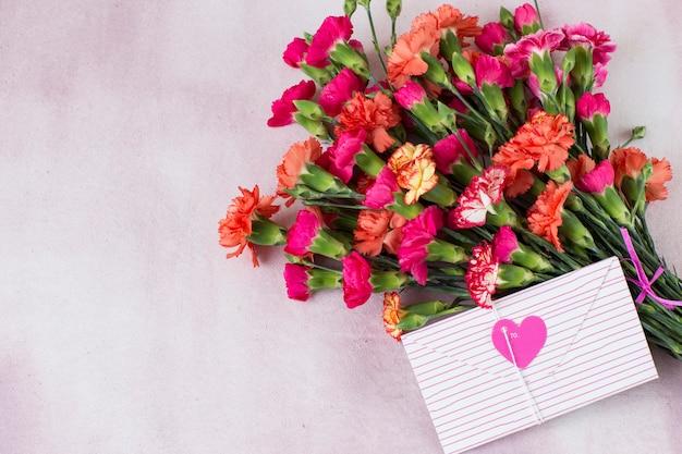 Rosas brilhantes sobre um fundo rosa e um envelope rosa com um coração