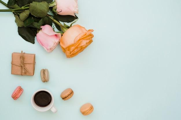 Rosas; caixa de presente; xícara de café e macaroons em fundo azul
