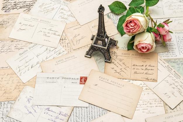 Rosas, cartões postais franceses antigos, carteiras e lembranças da torre eiffel de paris. fundo de férias sentimental nostálgico