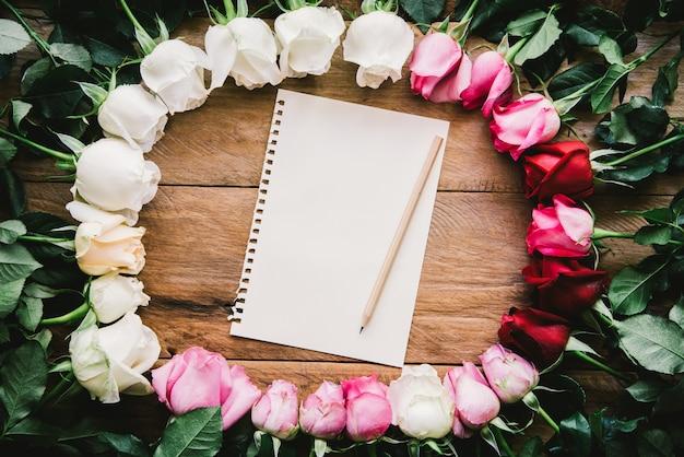 Rosas coloridas alinhadas em um papel de piso de madeira e lápis