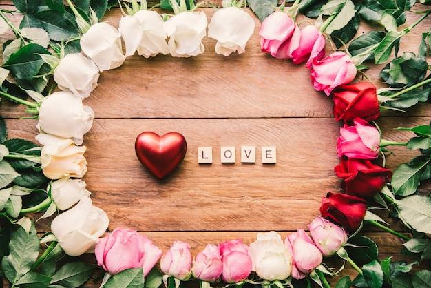 Rosas coloridas alinhadas em um piso de madeira com coração e palavra
