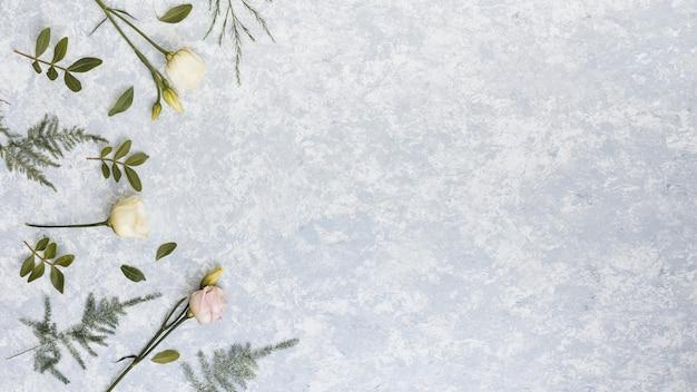 Rosas com ramos de plantas verdes na mesa