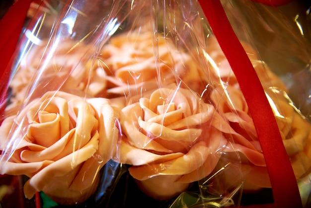 Rosas comestíveis de um ramalhete do chocolate branco no close-up do envolvimento de presente.