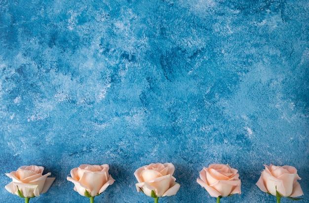 Rosas cor de pêssego em fundo acrílico azul e branco