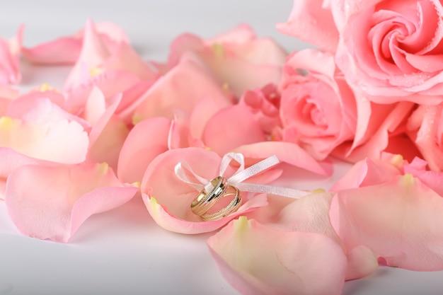 Rosas cor de rosa com anéis de casamento. fundo romântico de casamento