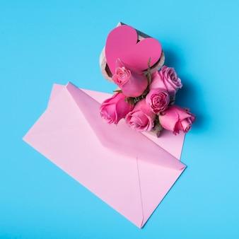 Rosas cor de rosa com envelope na mesa