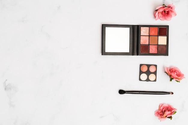 Rosas cor de rosa com pincel de maquiagem e paleta de sombra no fundo