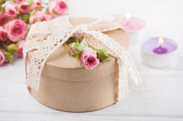 Rosas cor de rosa com presente e velas