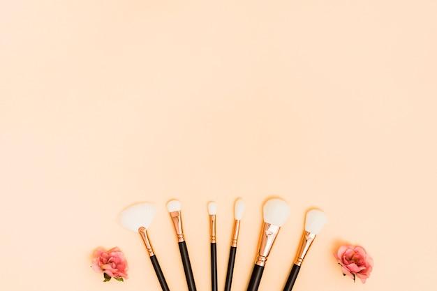 Rosas cor de rosa, decoradas com pincéis de maquiagem em pano de fundo bege
