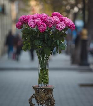 Rosas cor de rosa dentro de um vaso de vidro no meio da rua