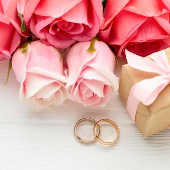 Rosas cor de rosa e alianças de casamento