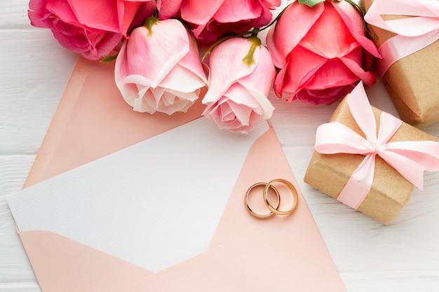 Rosas cor de rosa e anéis de casamento no envelope