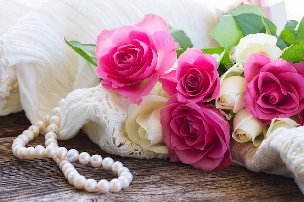 Rosas cor de rosa e brancas com rendas e pérolas na mesa de madeira