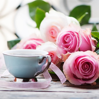 Rosas cor de rosa e café na mesa de madeira