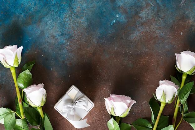 Rosas cor de rosa e caixa de presente em pedra