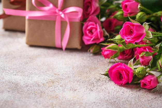 Rosas cor de rosa e caixas de presente com fitas