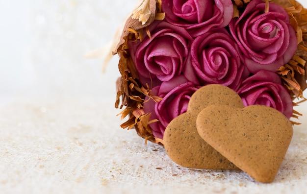 Rosas cor de rosa e cartão de detalhe de biscoitos em forma de coração com espaço para escrever