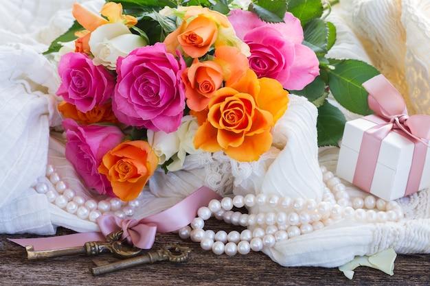 Rosas cor de rosa e laranja frescas com rendas e pérolas