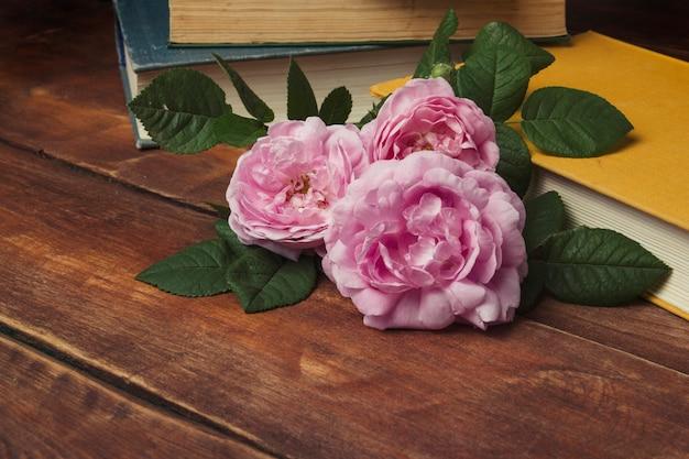 Rosas cor de rosa e livro com uma capa amarela sobre um fundo de madeira. o conceito de histórias e romances românticos