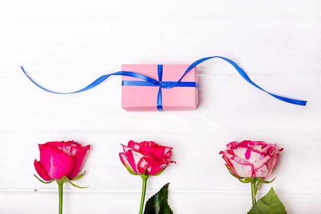 Rosas cor de rosa e presente isolado no fundo branco