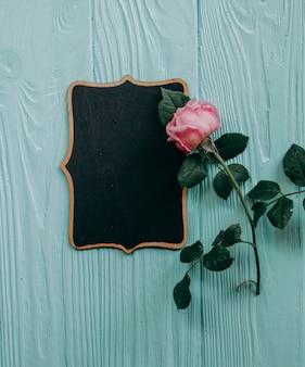 Rosas cor-de-rosa e um frame de retrato em uma tabela azul