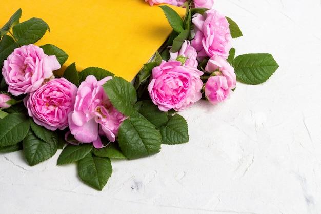 Rosas cor de rosa e um livro com uma capa amarela sobre uma superfície de pedra clara