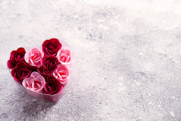 Rosas cor-de-rosa e vermelhas brilhantes feitas de aparas de sabão, em uma caixa em forma de coração.