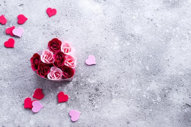 Rosas cor-de-rosa e vermelhas brilhantes feitas de aparas do sabão com corações na pedra, em uma caixa heart-shaped.