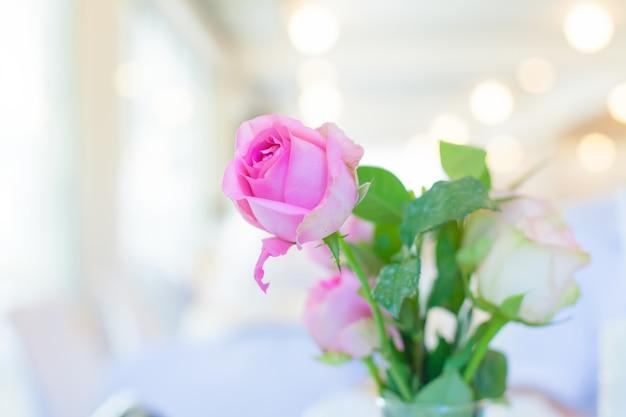 Rosas cor de rosa em copo de água na mesa branca