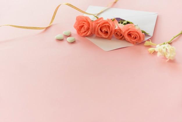 Rosas cor de rosa em envelope com corações na mesa