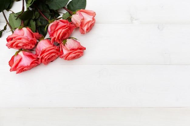 Rosas cor de rosa em fundo branco de madeira