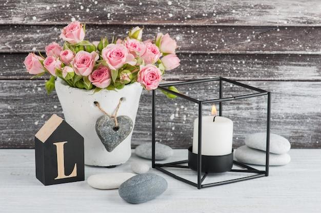 Rosas cor de rosa em panela de concreto com vela