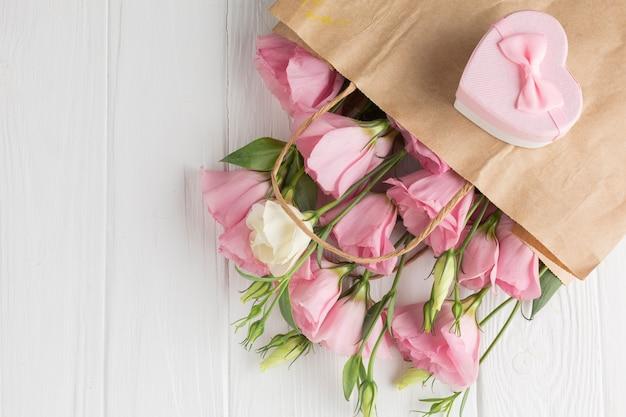 Rosas cor de rosa em um saco de papel com caixa de presente