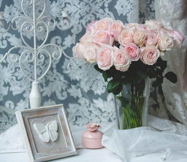 Rosas cor de rosa em um vaso de vidro com acessórios de casamento