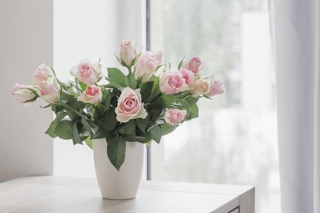 Rosas cor de rosa em um vaso na janela