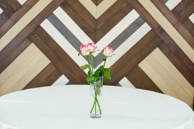 Rosas cor de rosa em um vaso transparente sobre uma toalha de mesa branca