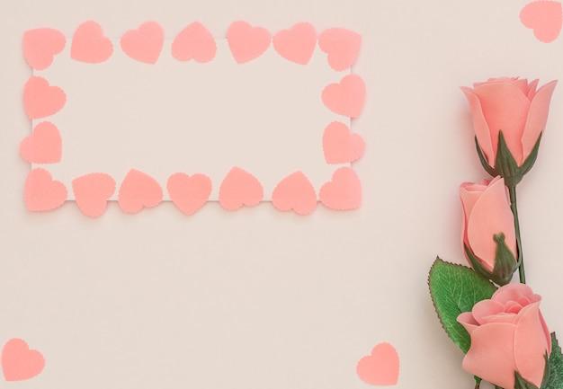 Rosas cor de rosa, folha em branco com moldura de corações rosa em fundo branco.