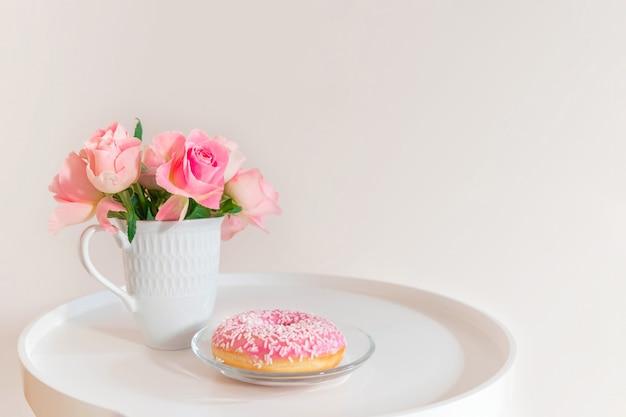 Rosas cor de rosa pastel em copo branco com rosquinha rosa na mesa de café branca