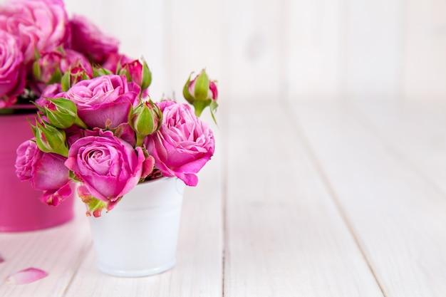 Rosas cor de rosa (peônia) em um vaso em fundo branco de madeira. flores
