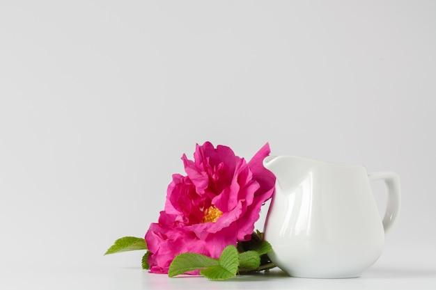 Rosas cor de rosa selvagens em um vaso na toalha de mesa branca