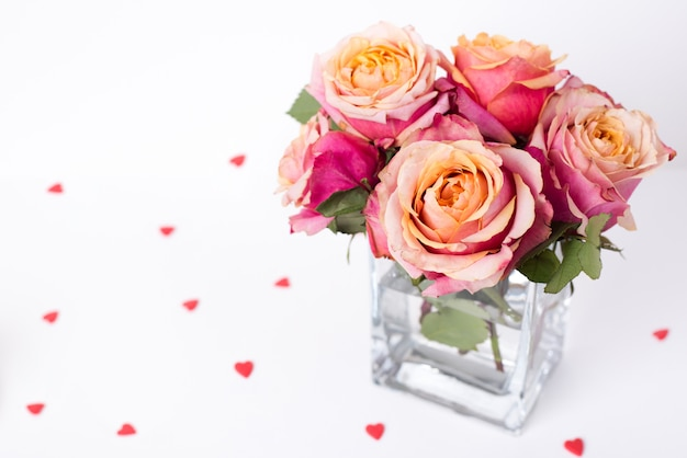 Rosas cor de rosa suaves e ornamentos de forma de coração