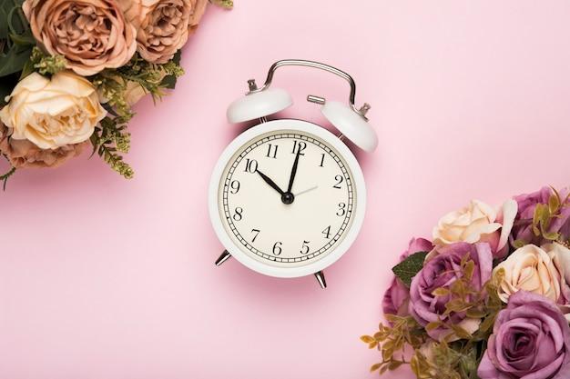 Rosas de flor ao lado do relógio