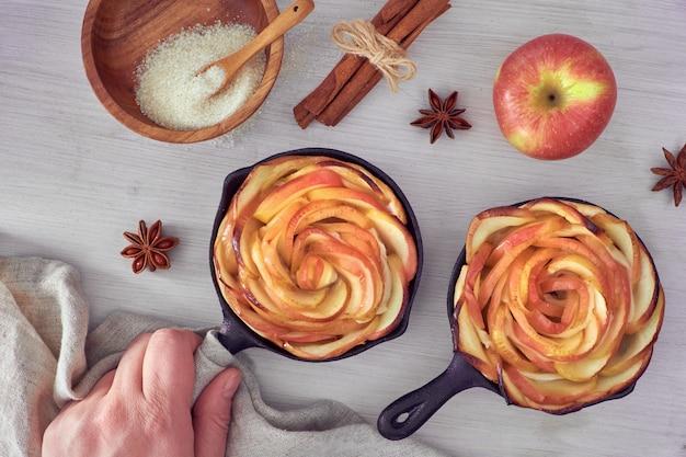 Rosas de maçã assada em frigideiras de ferro, vista superior na placa de madeira