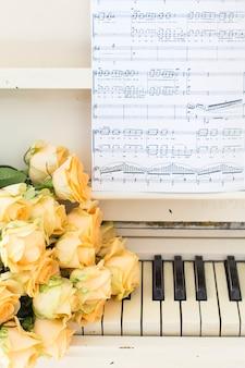 Rosas de pêssego no piano com notas